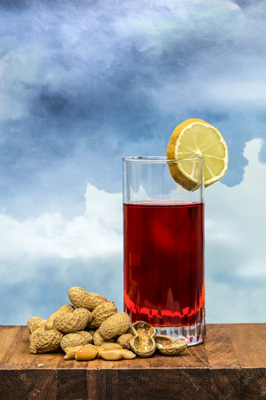 vermouth: glass of vermouth with  peanuts on a wood table over a blue sky Stock Photo