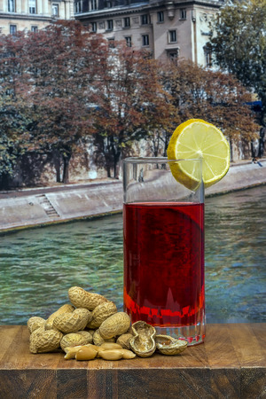 vermouth: glass of vermouth with  peanuts on a wood table over a view of a river Stock Photo