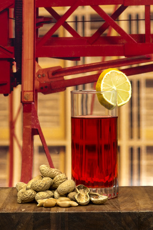 vermouth: glass of vermouth with  peanuts on a wood table over a construction crane Stock Photo