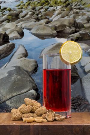 verm�: copa de vermut con los cacahuetes en una mesa de madera sobre rocas marinas de la costa