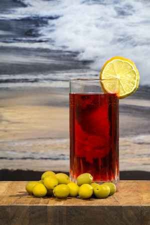 vermouth: glass of vermouth with olives on a wood table over a sunset on the beach