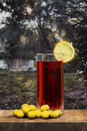 verm�: copa de vermut con aceitunas en una mesa de madera sobre un amanecer cerca del r�o Foto de archivo