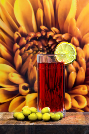 gigantic: glass of vermouth with olives on a wood table on a gigantic flower Stock Photo