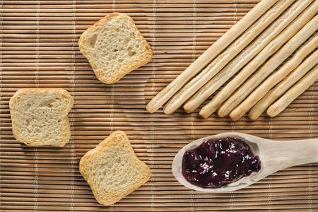 gressins: gressins, toasts et une cuillère de confiture de bleuets sur un tapis en osier