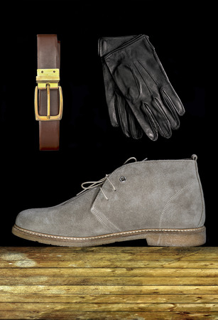suede belt: mens brown boots with strap and gloves on wooden boards and black background