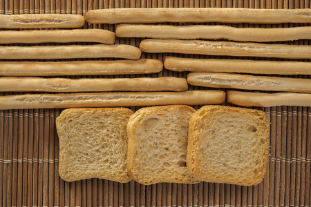 gressins: rows of breadsticks and toasts on a wicker mat