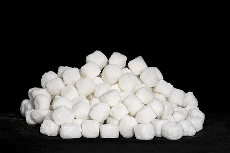 white cane: white cane sugar cubes stacked on a black background Stock Photo