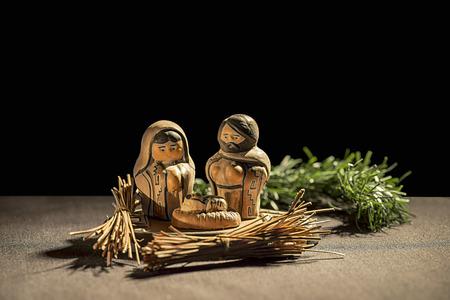 Crèche de Noel. Figures de l'Enfant Jésus, la Vierge Marie et saint Joseph sur un fond noir