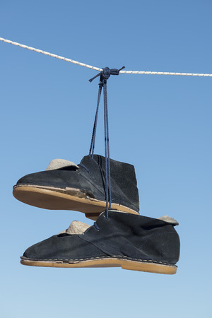 blue suede old boots hanging from a rope with blue sky background Imagens