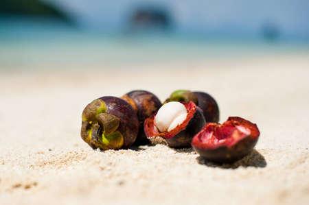 mangosteen: Four mangosteen on the tropical beach Stock Photo
