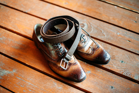 brown belt and leather shoes on wooden floor. Man accessories Stock Photo