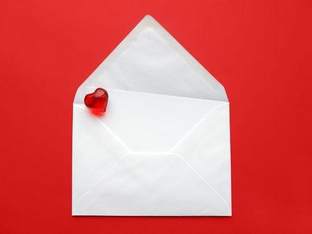 A white envelope with paper and heart on red