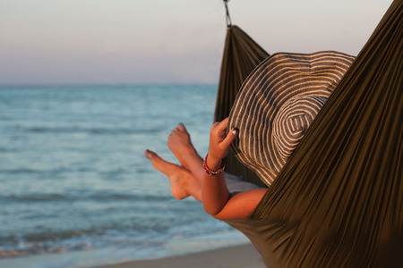 Woman relaxing on hammock with hat sunbathing on vacation. Against the background of the sea in the setting sun