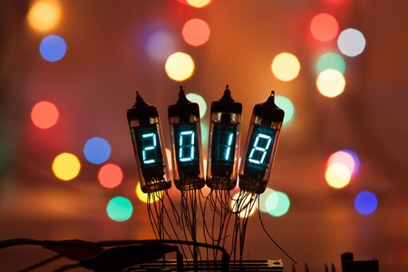 Happy new year is written with a lamp light. Radio electronic lamps. 2018. Original designed congratulation with a beautiful bokeh