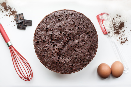 Bakery ingredients - flour, eggs, cocoa, chocolate on white table. Sweet pastry baking concept. Flat lay, copy space, top view.