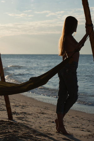 A girl stands near a hammock and look at the sea, rest, relaxation. dawn. Girl in jeans with long hair