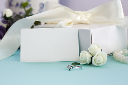 Styled stock photo. Feminine wedding desktop mockup. White roses, box with a bow, engagement ring, beads on pastel blue background. Copy space. Picture for blog