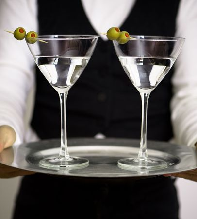 Two martini glasses on round silver tray