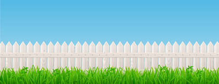 White wooden picket fence and green grass