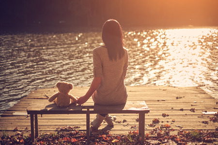Woman and teddy bear sitting bench