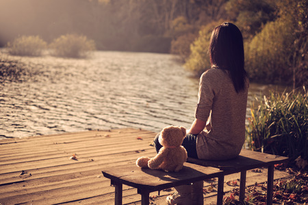 bear lake: Woman and teddy bear sitting bench