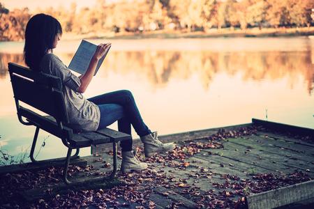 Meisje het lezen op een pier
