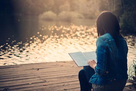 mujer leyendo libro: Lectura de la muchacha en un muelle Foto de archivo