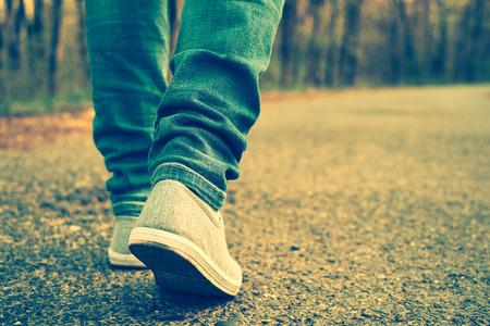 caminando: Pantalones vaqueros de mujer y zapatos de la zapatilla de deporte Foto de archivo