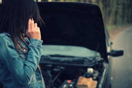 break down: Young caucasian woman with brown hair under the hood of her car break down