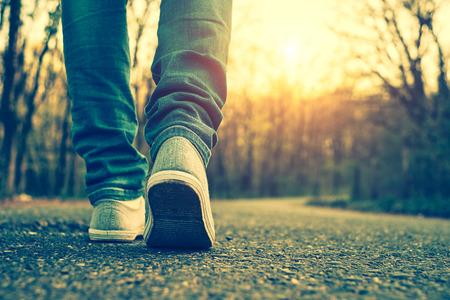 pasear: Pantalones vaqueros de mujer y zapatos de la zapatilla de deporte Foto de archivo
