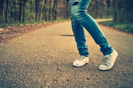 女性のジーンズとスニーカー靴