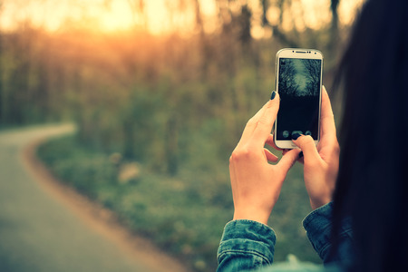 Portrait of beautiful young woman take a photo with mobile phone Standard-Bild