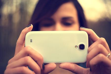 美しい若い女性の肖像画は、携帯電話で写真を撮る