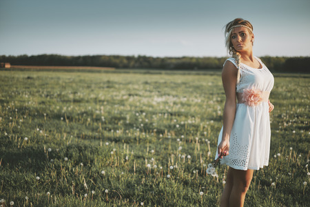 Beautiful young girl in dress on the spring meadow photo