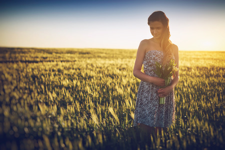 Young woman on wheat field holding white flower photo