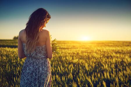 小麦フィールド持株白い花の若い女性 写真素材