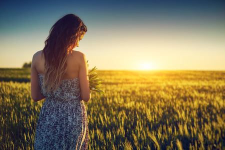 Young woman on wheat field holding white flower