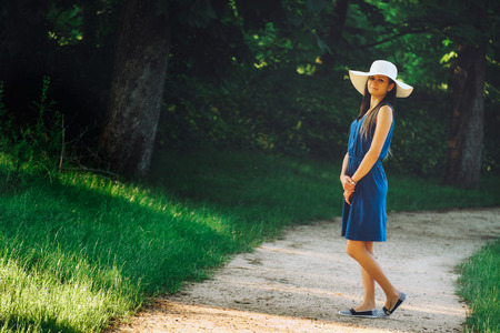 Attractive young adult woman in outdoor blue dress photo