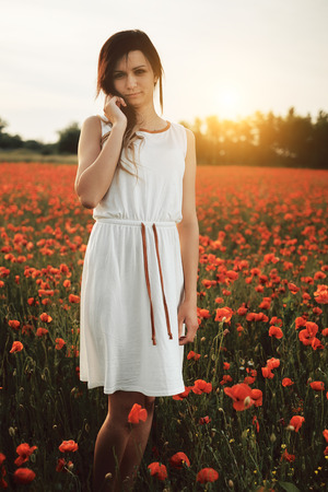 Beautiful young girl on poppy field with dress photo