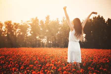 field of flowers: Young girl on poppy field hands up