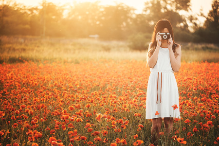 Girl taking picture on poppy field photo