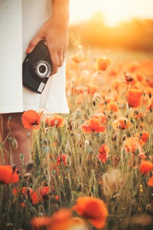 Vintage camera in woman hand on poppy field