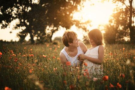 Mother and daughter on poppy field photo