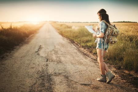 Attractive backpacker girl looking map Standard-Bild