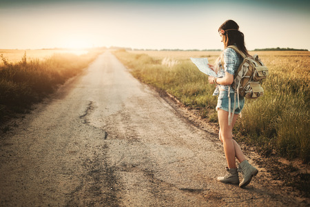 Attractive backpacker girl looking map Foto de archivo
