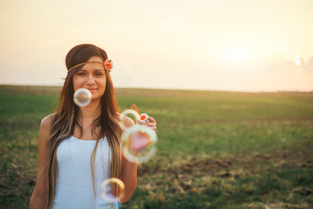 blowing bubbles: Woman blowing bubbles Stock Photo