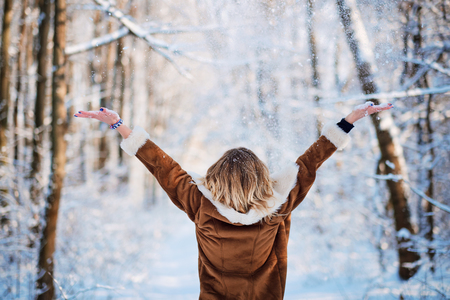 Blonde young woman standing in snowfall Stock Photo