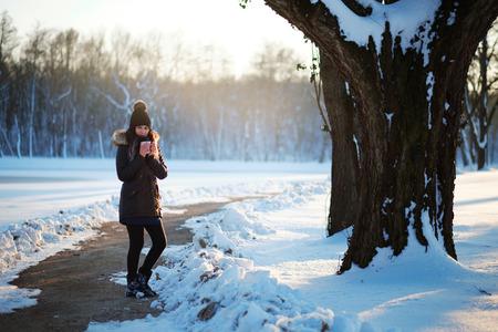 chocolate caliente: Mujer que sostiene t� caliente en invierno parque cubierto de nieve Foto de archivo
