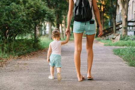 Mother with little daughter walking in the park