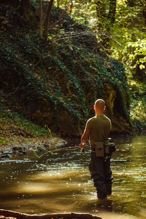 A fisherman fishing with fly fishing in the flowing stream Stock fotó